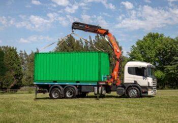 camion con hidrogrua y container verde en el campo