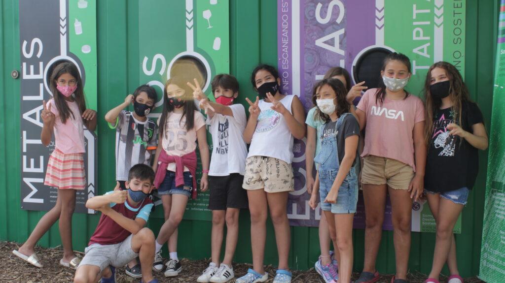 Grupo de niños y niñas frente a un punto de acopio de reciclables