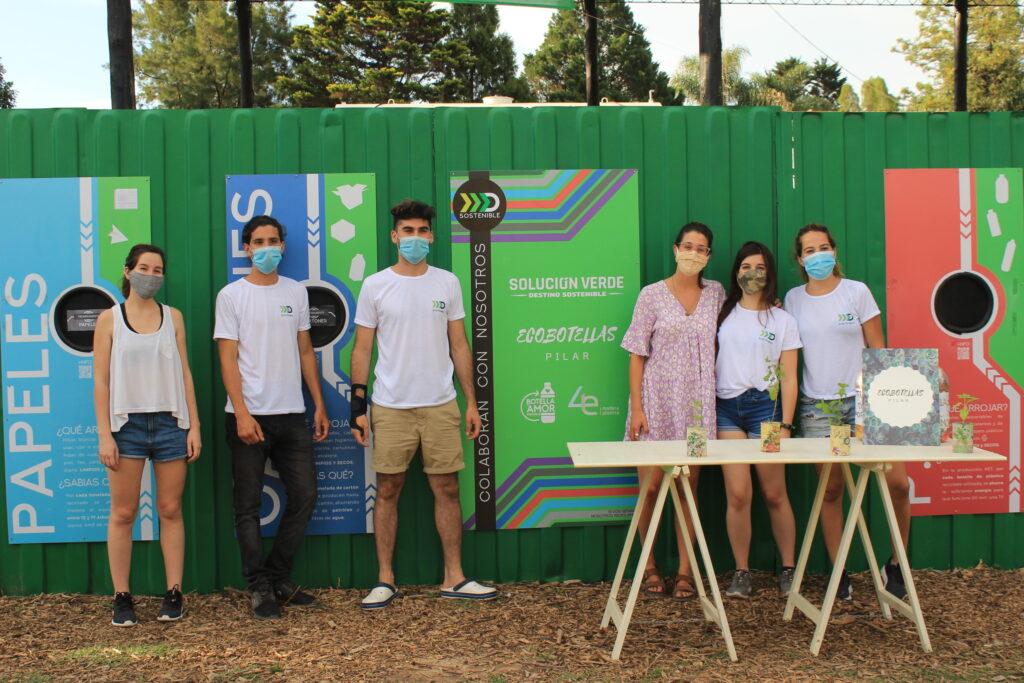 Foto de 6 personas con barbijo frente a un punto de acopio de reciclables. A la derecha el espacio destinado a reciclar plástico PET.