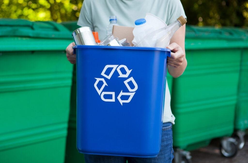 Foto de una persona sosteniendo un tacho con reciclables.
