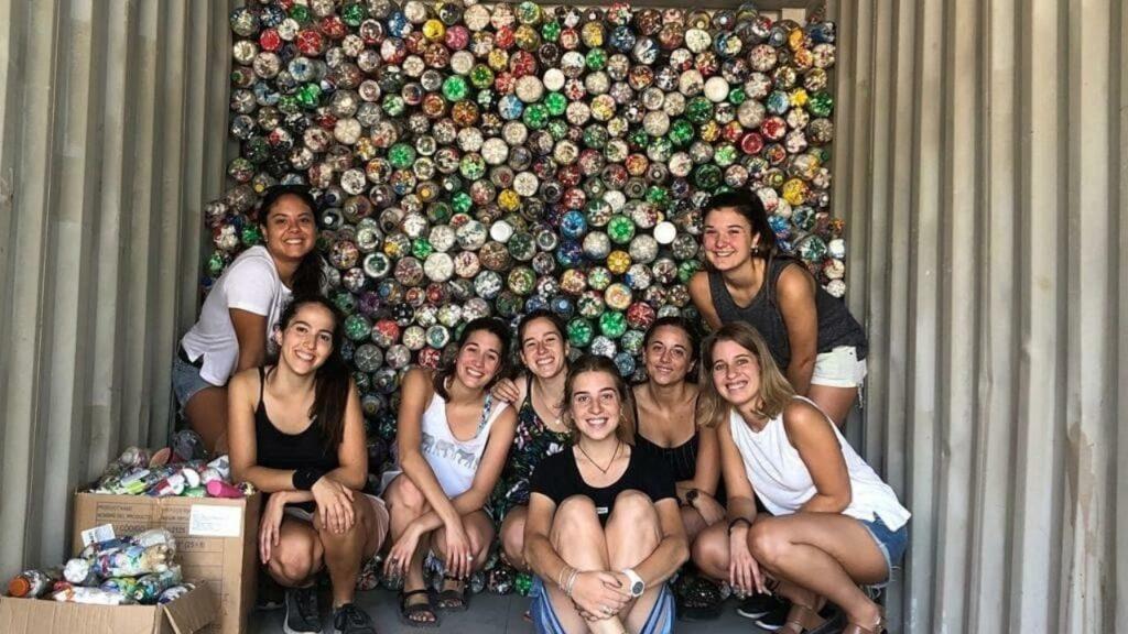 5 chicas jóvenes frente al fondo de un container con eco-botellas apiladas cubriendo totalmente la pared trasera del mismo. son representantes de Ecobotellas Pilar, de Solución Verde y voluntarias .
